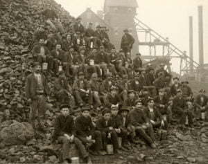Miners pose with lunch pails in hand on a mine rock pile outside of the Tamarack mineshaft.