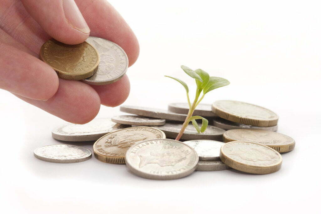A seedling sprouting from a small pile of coins. A hand is placing more coins on the pile.